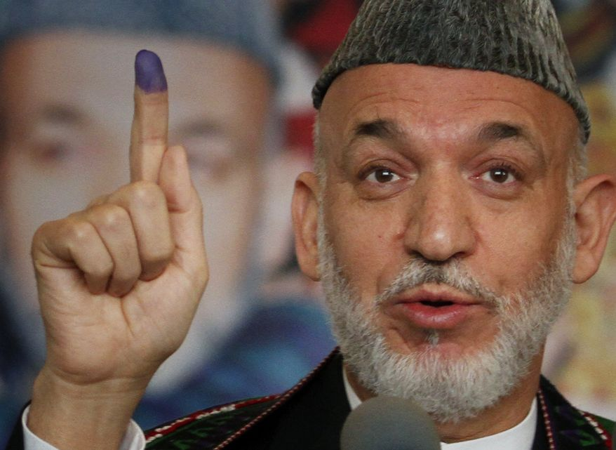 Afghan President Hamid Karzai displays his inked finger after casting his vote, as he speaks to media at a polling station in Kabul, Afghanistan, Saturday, Sept. 18, 2010. (AP Photo/Musadeq Sadeq)