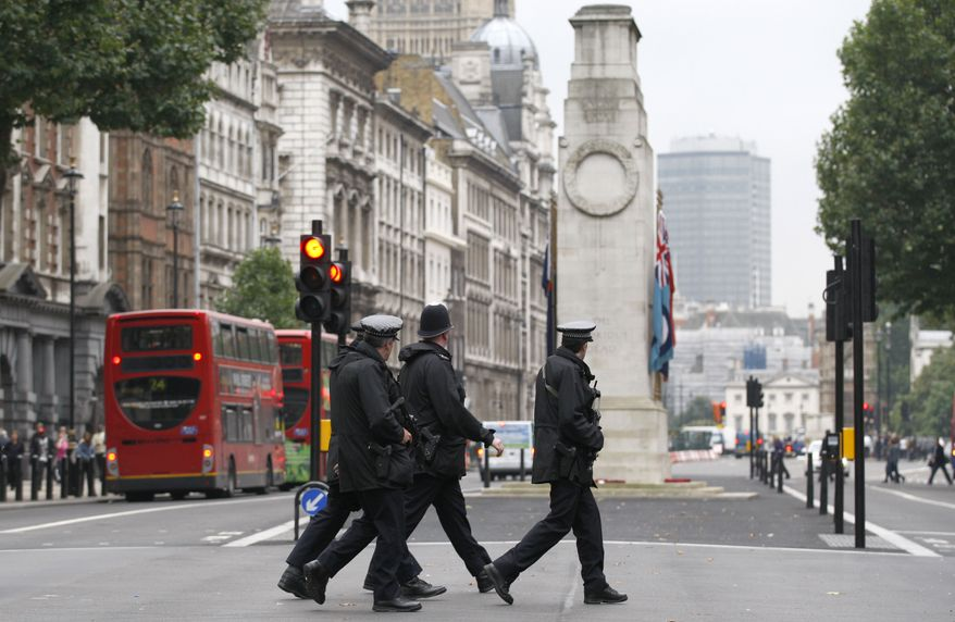 Armed police officers walk across Whitehall in front of the Cenotaph war memorial in London on Monday, Oct. 4, 2010. (AP Photo/Sang Tan)