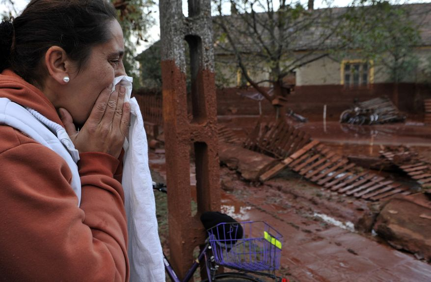 A Hungarian woman reacts while seeing her home flooded by toxic mud in Devecser, Hungary, on Tuesday, Oct. 5, 2010. Monday's flooding was caused by the rupture of a red sludge reservoir at the Ajkai Timfoldgyar alumina plant in western Hungary. (AP Photo/Bela Szandelszky)