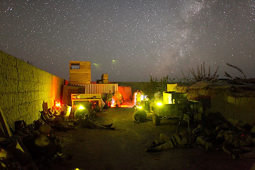 In this photo taken Tuesday, Oct. 13, 2009, U.S. Marines with Alpha Company-Task Force Raider, 2nd Recon Battalion lie down inside a small patrol base during a pause in an all night mission in Helmand province, southern Afghanistan. Task Force Raider is a strike force which conducts raids targeting Taliban networks in the Helmand province. (AP Photo/Brennan Linsley, File)