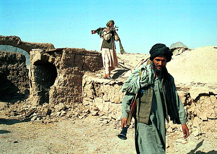 In this Friday Nov. 2, 2001 file picture, Taliban fighters, one carrying a rocket-propelled grenade launcher, foreground, and one carrying a heavy machine gun, walk through the ruins of a mud house near Kandahar, Afghanistan. (AP Photo, File)
