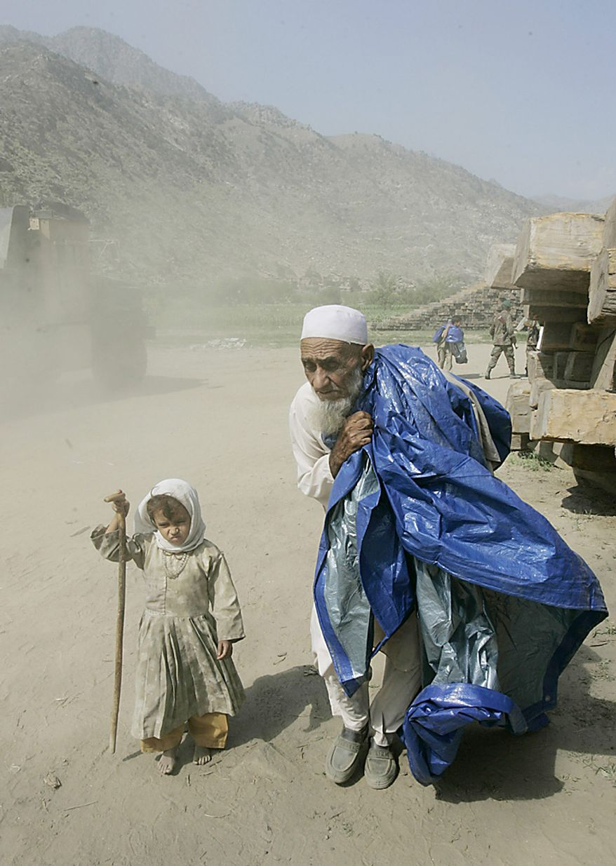 n this Sunday, Sept. 10, 2006 file picture, a girl holds her grandfather's cane as he carries aid supplies distributed by the U.S. Army at Kandagal, Afghanistan. (AP Photo/Saurabh Das, File)
