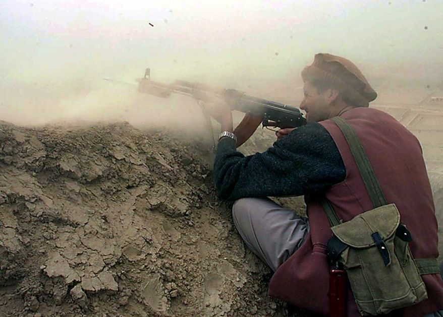 In this Wednesday, Oct. 10, 2001 file picture, a fighter with the northern-based alliance opposed to Afghanistan's Taliban rulers fires at Taliban positions on a frontline outpost in northern Takhar province in Puli Khumri Hill, Afghanistan, about 50 kilometers (31 miles) from the border with Tajikistan. (AP Photo/Misha Japaridze, File)