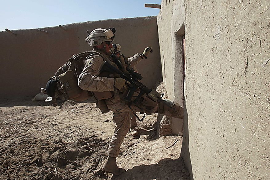 In this Wednesday Feb. 17, 2010 file picture, U.S. Marine Staff Sgt. Christopher Whitman, from Clearwater, Fla., and from 3rd Battalion, 6th Marine Regiment kicks in a door to search a compound while on a patrol in Marjah in Afghanistan's Helmand province. (AP Photo/David Guttenfelder, File)