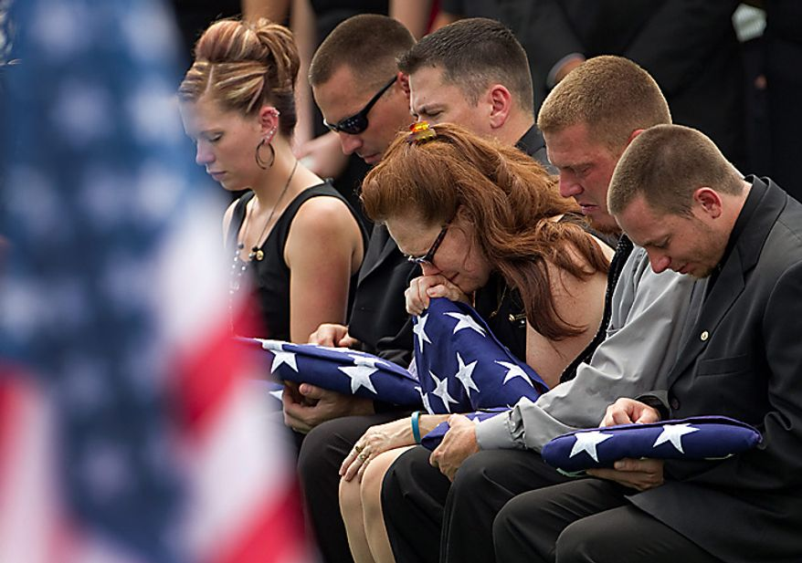 In this Monday, July 19, 2010 file picture, Beverly A. Crow, center, sits with unidentified family members during the funeral for her husband, Missouri Army National Guard Sgt. Robert Wayne Crow in Liberty, Mo. Sgt. Crow, 42, of Kansas City, Mo., died July 10 in Paktika, Afghanistan, of wounds suffered when insurgents attacked his vehicle with an improvised explosive device. He was a combat engineer with the 203rd Engineer Battalion headquartered in Joplin, Mo. (AP Photo/Charlie Riedel, File)