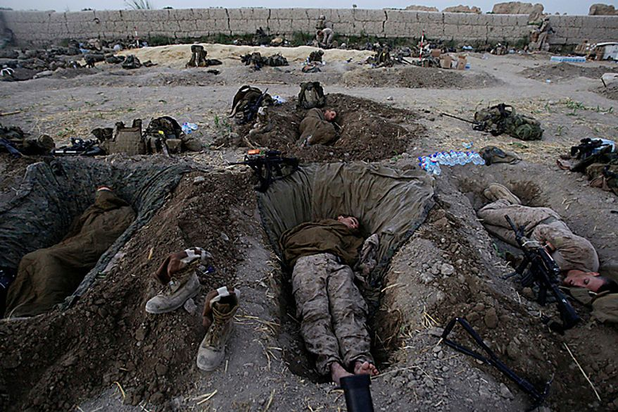 In this July 8, 2009 file photo, U.S. Marines from the 2nd MEB, 1st Battalion 5th Marines sleep in their fighting holes inside a compound where they stayed for the night, in the Nawa district of Afghanistan's Helmand province. (AP Photo/David Guttenfelder, File)