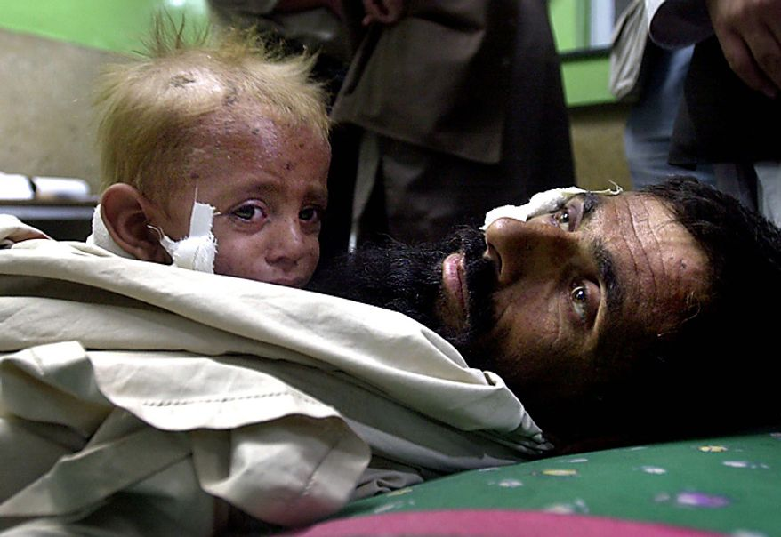 In this Sunday, Oct. 14, 2001 file picture, 1-year-old Azizullah lies in the arms of his father Ahmanzai at the hospital in the city of Jalalabad, Afghanistan. They were allegedly wounded in the village of Karam, some 50 km (30 miles) west of Jalalabad, Afghanistan during a U.S. air attack. According to the Taliban government, who organized a visit to the village by foreign journalists, around 200 civilians were killed in Karam on Thursday, during a U.S. air attack. (AP Photo/Enric Marti, File)