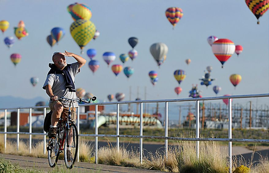 An unidentified bicyclist watches the mass ascension of hot air balloons while on a early morning bike ride along the North Diversion Channel path during the first morning of the Albuquerque International Balloon Fiesta, Saturday, Oct. 2, 2010, in Albuquerque, N.M. (AP Photo/Albuquerque Journal, Marla Brose)