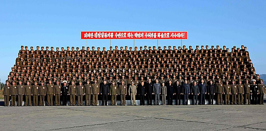 In this undated photo released on Wednesday, Oct. 6, 2010 by Korean Central News Agency via Korea News Service, North Korean leader Kim Jong Il wearing sunglasses at center front and his third son Kim Jong Un wearing black suit, standing third from Kim Jong Il's left, pose with North Korean soldiers who participated in  a coordinated drill of a military unit of the Korean People's Army at an undisclosed location in North Korea.  North Korea's heir apparent observed military drills with his father, according to a state media report Tuesday, heralding a growing public profile for Kim Jong Un as he takes on a more prominent role in the reclusive nation. Chief of the General Staff of the Korean People's Army Ri Yong Ho stands at first from Kim Jong Il's left and Defense Chief Kim Yong Chun stands at second from Kim Jong Il's left. (AP Photo/Korean Central News Agency via Korea News Service)