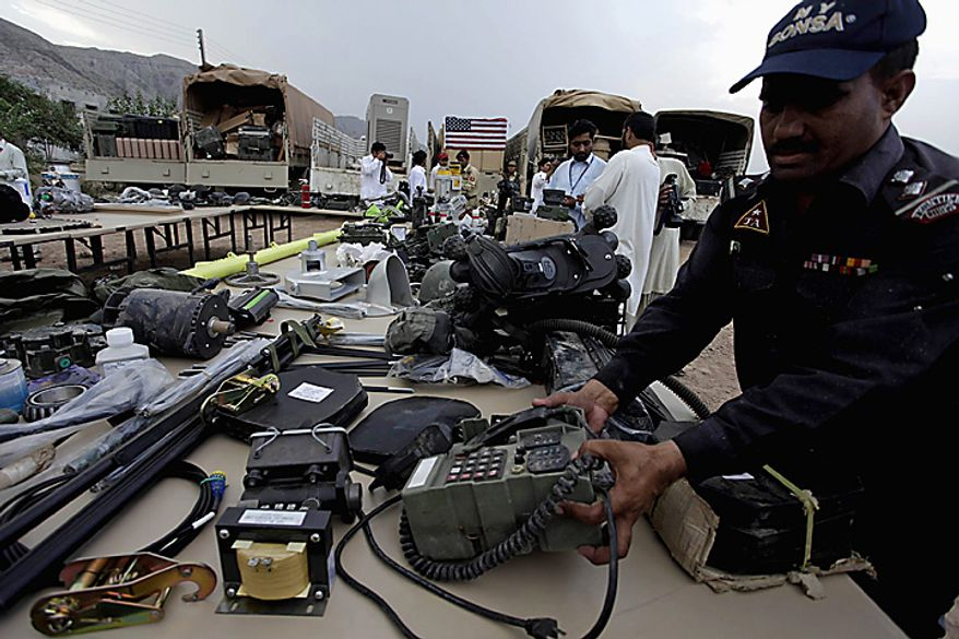 In this picture taken on Sept. 27,  2010, a soldier of Pakistani para military force arranges equipment stolen from NATO trucks, displayed for media in Peshawar, Pakistan. drivers stand at a terminal where NATO containers are kept in Peshawar, Pakistan. Pakistan blocked a vital supply route for U.S. and NATO troops in Afghanistan in apparent retaliation for an alleged cross-border helicopter strike by the coalition that killed three Pakistani frontier troops. (AP Photo/Mohammad Sajjad)