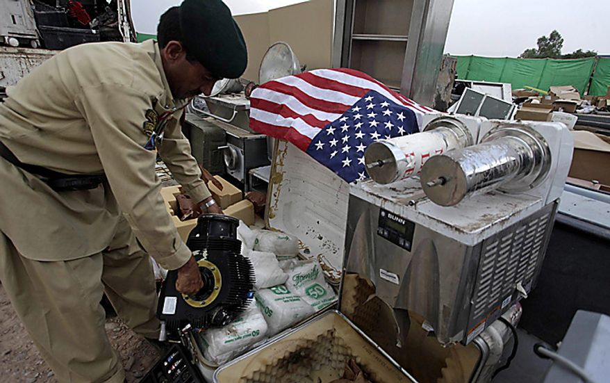 In this picture taken on Sept. 27,  2010, a soldier of Pakistani para military force arranges equipment stolen from NATO trucks to display for the media in Peshawar, Pakistan. Drivers stand at a terminal where NATO containers are kept in Peshawar, Pakistan. Pakistan blocked a vital supply route for U.S. and NATO troops in Afghanistan in apparent retaliation for an alleged cross-border helicopter strike by the coalition that killed three Pakistani frontier troops. (AP Photo/Mohammad Sajjad)