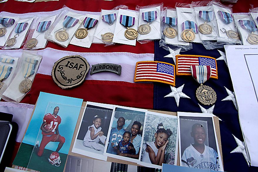 In this picture taken on Sept. 27,  2010, medals and photographs stolen from NATO trucks, are displayed for the media in Peshawar, Pakistan. Pakistan blocked a vital supply route for U.S. and NATO troops in Afghanistan in apparent retaliation for an alleged cross-border helicopter strike by the coalition that killed three Pakistani frontier troops. (AP Photo/Mohammad Sajjad)