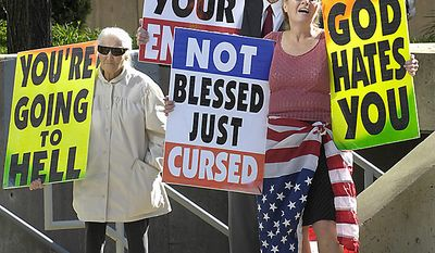 In this Oct. 31, 2007 file photo, Margie M. Phelps, left, stands with her husband Pastor Fred Phelps and her daughter Margie J. Phelps during a demonstration outside the federal courthouse in Baltimore. Margie J. Phelps is set to go before the U.S. Supreme Court on Wednesday, Oct. 5, 2010, to represent her church in a case that tests the scope of free speech protections under the Constitution's First Amendment. (AP Photo/Baltimore Sun, Jed Kirschbaum)