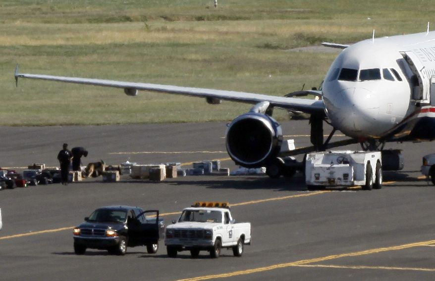 Law enforcement authorities search a US Airways Airbus A319 jet on a taxiway at Philadelphia International Airport in Philadelphia on Thursday, Oct. 7, 2010, after reports that someone without a security badge was helping load the Bermuda-bound plane. (AP Photo/Matt Rourke)
