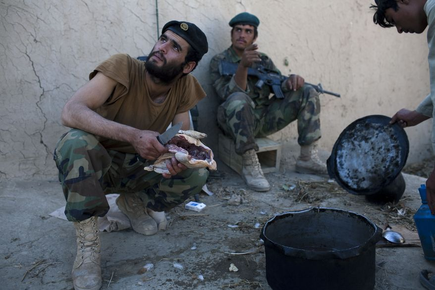 Afghan soldiers attached to Bravo Company 2-502 Infantry Regiment, 101st Airborne Division, prepare lunch at an outpost near Forward Operation Base Howz-e-Madad in the Zhari district of Afghanistan's Kandahar province on Wednesday, Oct. 6, 2010. (AP Photo/Rodrigo Abd)