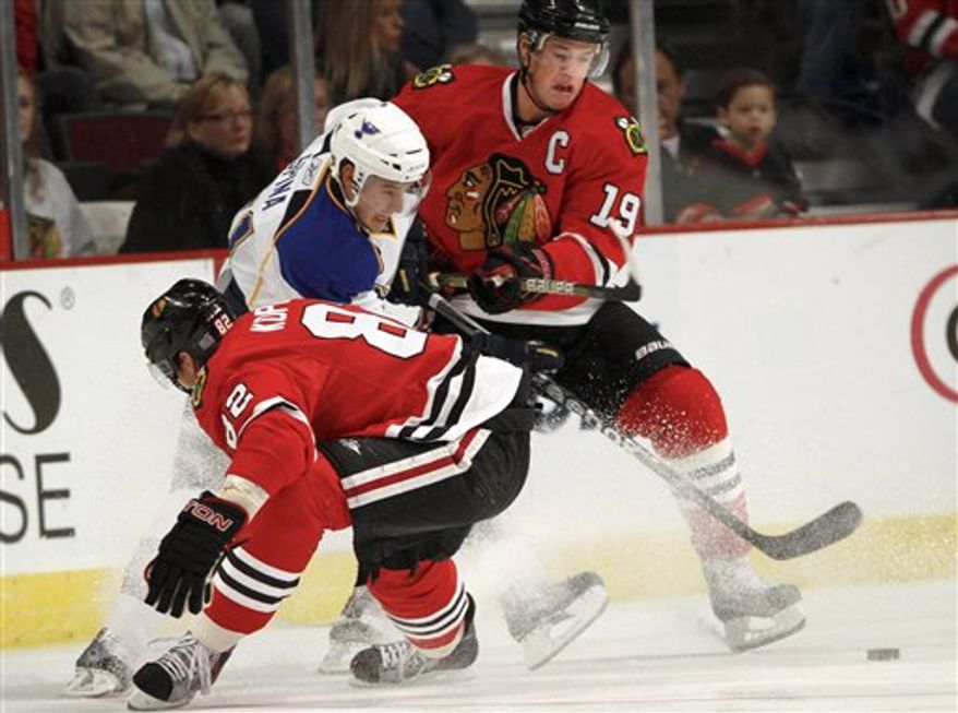 St. Louis Blues' David Spina gets squeezed between Chicago Blackhawks' Tomas Kopecky, left, and Jonathan Toews during the first period of a preseason NHL hockey game Sunday, Oct. 3, 2010, in Chicago. (AP Photo/Charles Cherney)