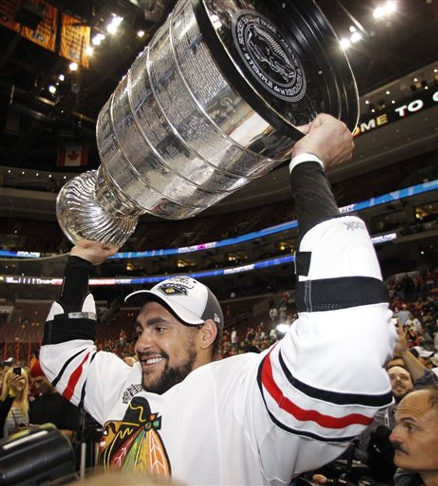 FILE - In this June 9, 2010, file photo, Chicago Blackhawks right wing Dustin Byfuglien lifts the Stanley Cup after the Blackhawks beat the Philadelphia Flyers in Game 6 to win the NHL hockey Stanley Cup in Philadelphia. Byfuglien is no longer with the Blackhawks - he is one of several players traded or let go in the days following the team's title because they couldn't all fit under the salary cap. (AP Photo/Matt Slocum, File)