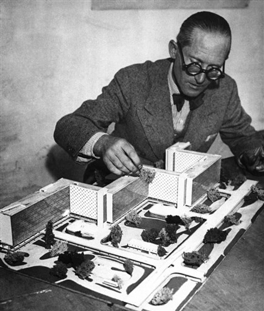 FILE - In this Jan. 18, 1949 file photo Swiss-born architect Le Corbusier sits in his office in Paris. Le Corbusier's legacy faces a tense re-examination in his home nation after Switzerland's largest bank dropped an ad campaign featuring the modernist pioneer earlier this week. The debate has nothing to do with aesthetics and focuses solely on politics. Letters made public in recent years and a 2008 biography suggest that the architect  was a sympathizer of Hitler's Nazi regime whose Fascist tendencies went far beyond what was previously known. His real name was Charles Edouard Jeanneret. (AP Photo)