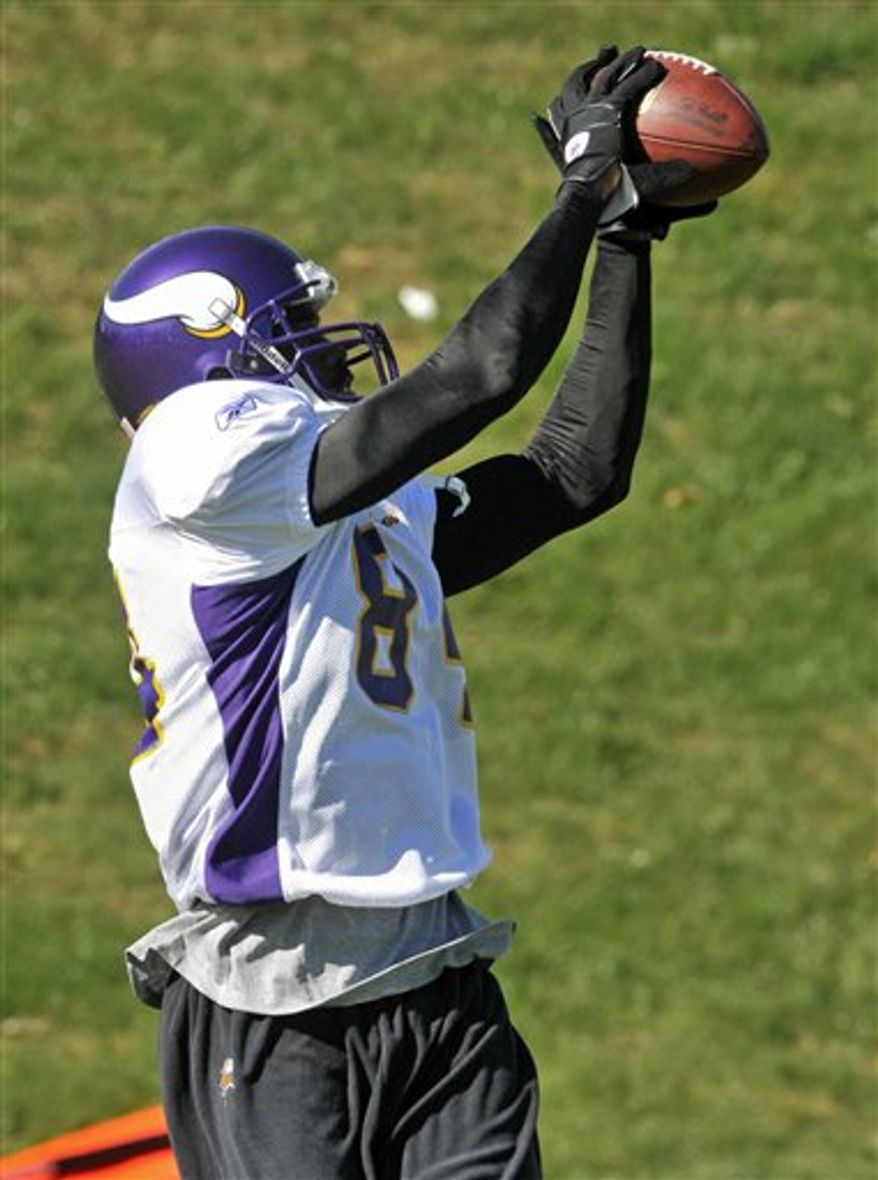 Minnesota Vikings quarterback Brett Favre, left, throws to wide receiver Randy Moss during NFL football practice, Thursday, Oct. 7, 2010 in Eden Prairie, Minn. Moss was traded Wednesday to the Vikings by the New England Patriots. (AP Photo/Jim Mone)