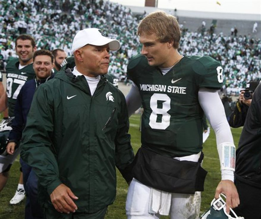 Quarterback Kirk Cousins was taken in the fourth round of the NFL draft by the Washington Redskins on Saturday. He's shown here with Michigan State offensive coordinator Don Treadwell in 2010. (AP Photo/Al Goldis)