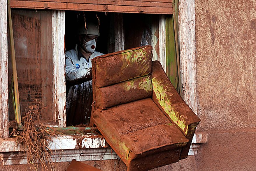A  worker, wearing a protective gear,discards furniture from a house damaged by flooding toxic mud in the village of Kolontar, Hungary, Thursday, Oct. 7, 2010. Monday's flooding was caused by the rupture of a red sludge reservoir at a metals works in western Hungary and has affected seven towns near the Ajkai, 100 miles (160 kilometers) southwest of Budapest. The flood of toxic mud killed a yet unknown number of people, injured more than one hundred, with some people still missing. (AP Photo/Bela Szandelszky)
