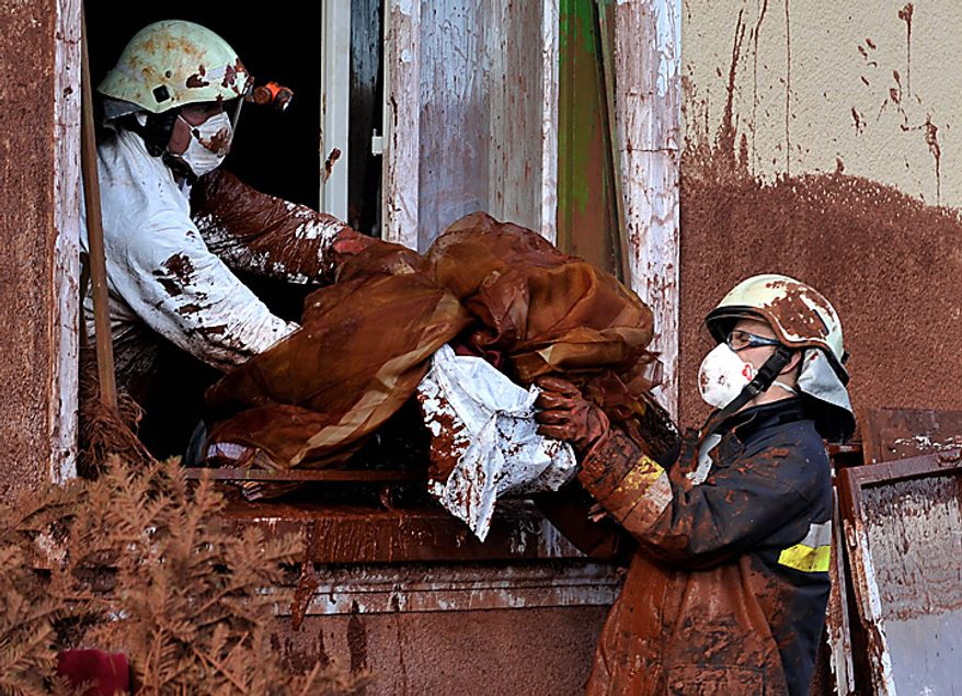 Firefighters, wearing protective gear, discard belongings from a house damaged by flooding toxic mud in the village of Kolontar, Hungary, Thursday, Oct. 7, 2010. Monday's flooding was caused by the rupture of a red sludge reservoir at a metals works in western Hungary and has affected seven towns near the Ajkai, 100 miles (160 kilometers) southwest of Budapest. The flood of toxic mud killed a yet unknown number of people, injured more than one hundred, with some people still missing. (AP Photo/Bela Szandelszky)