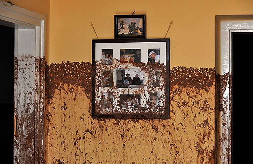 Family photos on a wall show the height of the sludge after a flood of toxic mud broke into a home in the village of Kolontar, Hungary, Thursday, Oct. 7, 2010. Monday's flooding was caused by the rupture of a red sludge reservoir at a metals works in western Hungary and has affected seven towns near the Ajkai, 100 miles (160 kilometers) southwest of Budapest. The flood of toxic mud killed a yet unknown number of people, injured more than one hundred, with some people still missing. (AP Photo/Bela Szandelszky)
