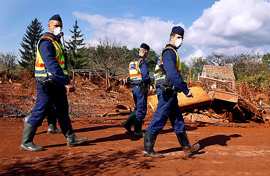 Hungarian police patrol a street flooded by toxic mud in Kolontar, Hungary, Thursday, Oct. 7, 2010. The toxic red sludge that burst out of a Hungarian factory's reservoir and inundated three villages reached the mighty Danube on Thursday after wreaking havoc on smaller rivers and creeks, an emergency official said. The reservoir break Monday disgorged a toxic torrent into creeks that flow into waterways connected to the Danube. Creeks in Kolontar, the western Hungarian village closest to the spill site, were swollen ochre red days later and villagers said they were devoid of fish. (AP Photo/Darko Bandic)
