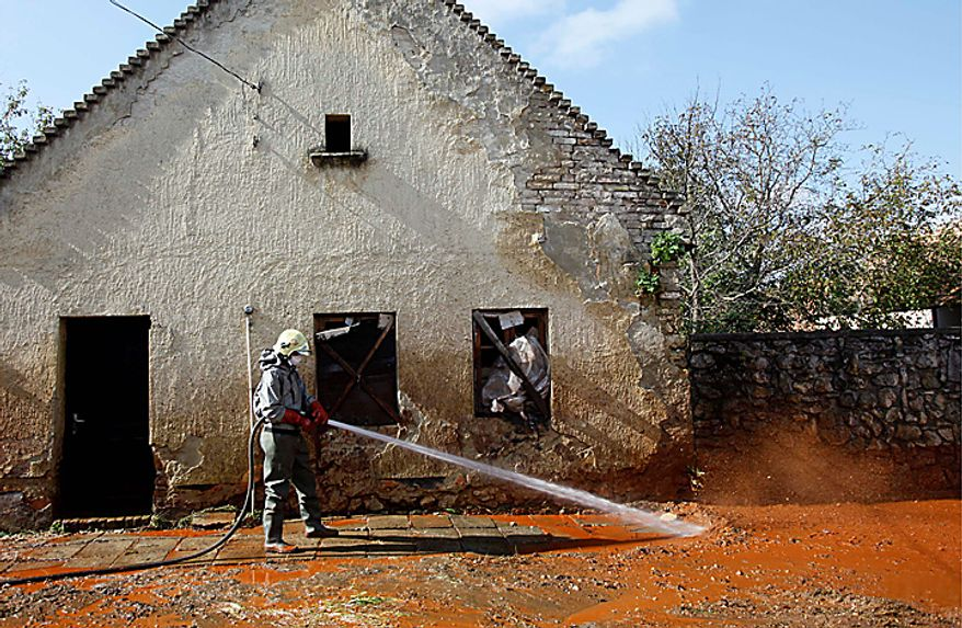 A Hungarian fire fighter cleans a street flooded with toxic mud in Devecser, Hungary, Thursday, Oct. 7, 2010. The toxic red sludge that inundated three Hungarian villages reached Europe's mighty Danube River on Thursday but no immediate damage was evident, Hungary's rescue operations agency said. The European Union and environmental officials had feared an environmental catastrophe affecting half a dozen nations if the red sludge, a waste product of making aluminum, contaminated Europe's second-longest river after bursting out of a factory's reservoir. (AP Photo/Darko Bandic)