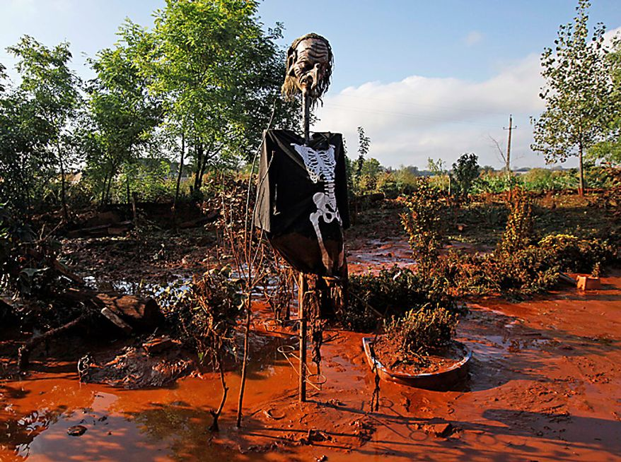 A scarecrow is seen in a yard flooded by toxic mud in Devecser, Hungary, Thursday, Oct. 7, 2010. The toxic red sludge that inundated three Hungarian villages reached Europe's mighty Danube River on Thursday but no immediate damage was evident, Hungary's rescue operations agency said. The European Union and environmental officials had feared an environmental catastrophe affecting half a dozen nations if the red sludge, a waste product of making aluminum, contaminated Europe's second-longest river after bursting out of a factory's reservoir. (AP Photo/Darko Bandic)
