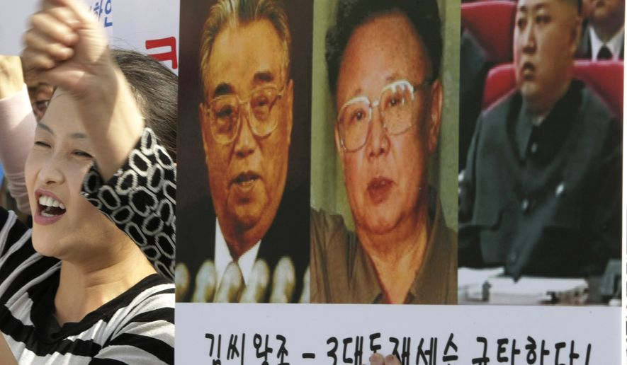 """A North Korean defector shouts slogans next to a placard showing photos of North Korean leader Kim Jong-il, center, his late father Kim Il-sung, left, and his youngest son Kim Jong-un, during a rally against the North's succession in Seoul, South Korea, Friday, Oct. 8, 2010. The letters on a banner read """"We denounce the family's succession through three generations."""" (AP Photo/Ahn Young-joon)"""