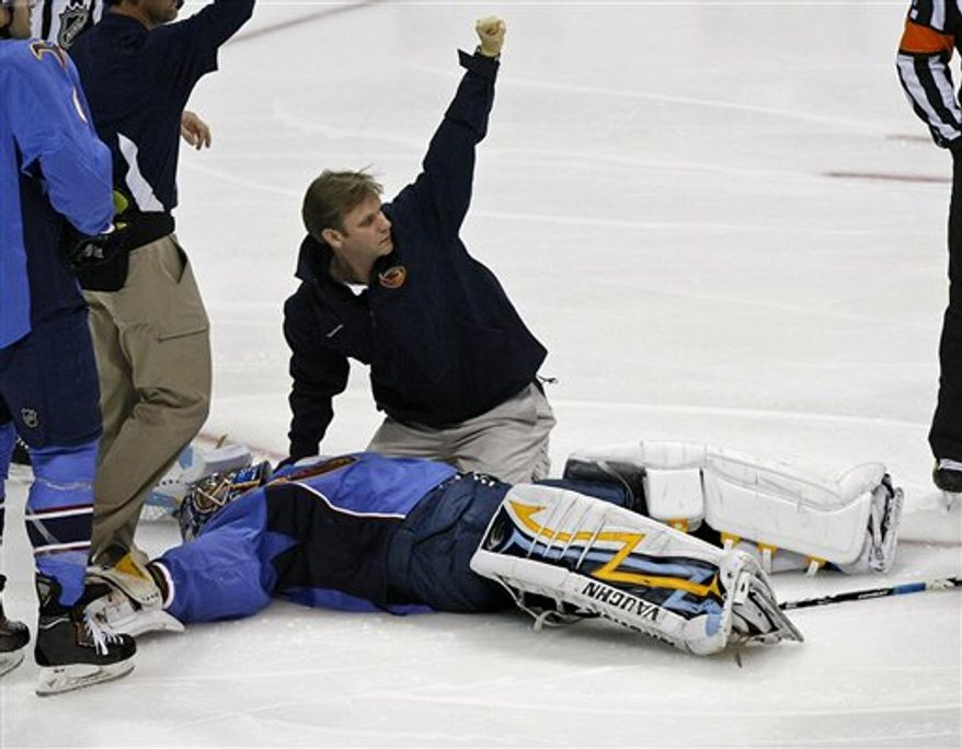 The Atlanta Thrashers hockey team gathers around goalie Ondrej Pavelec as he is placed on a stretcher after he collapsed to the ice in the first period of an NHL game between the Thrashers and Washington Capitals, Friday, Oct. 8, 2010, in Atlanta, Ga.   Pavelec collapsed to the ice in the early minutes of the season-opening game against the Capitals The team said the 23-year-old Pavelec lost consciousness and was taken to a hospital for further evaluation. Thrashers officials released no other information on his condition. (AP Photo/Atlanta Journal & Constitution,  Curtis Compton)