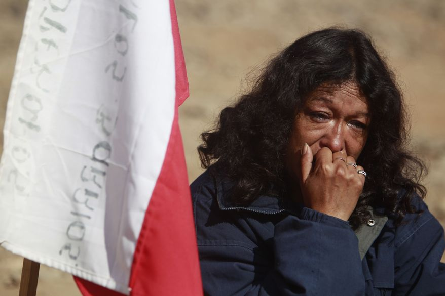 A relative reacts after it was announced that a drill reached the trapped miners at the San Jose Mine near Copiapo, Chile, on Saturday, Oct. 9, 2010. A drill reached the miners at a point 2,041 feet (622 meters) below the surface at 8:05 a.m., after 33 days of drilling. (AP Photo/Natacha Pisarenko)