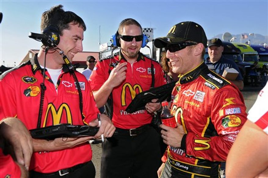 Jamie McMurray, right, talks with members of his crew signs after he took the pole position during qualifying for the Pepsi Max 400 NASCAR car race, Friday, Oct. 8, 2010, in Fontana, Calif.  (AP Photo/Mark J. Terrill)