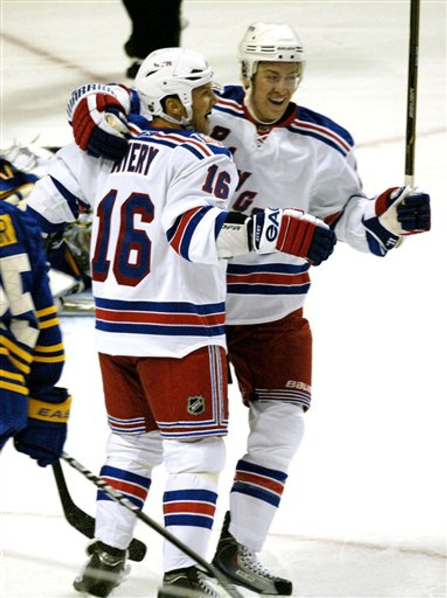 New York Rangers left winger Sean Avery, left, celebrates Rangers Derek Stepan's goal against Buffalo Sabres goalie Ryan Miller, right, during the first period of an NHL hockey game in Buffalo, N.Y. on Saturday, Oct. 9, 2010. (AP Photo/Don Heupel)