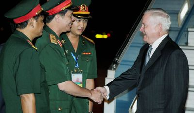 Defense Secretary Robert M. Gates is greeted by (from left) Senior Col. Nguyen Hong Quang, Maj. Gen. Nguyen Huu Manh and 2nd Lt. Nguyen Thang Anh as he deplanes from a U.S. military aircraft upon his arrival at the Noi Bai International Airport in Hanoi on Sunday. Mr. Gates is in Vietnam to reassure jittery Southeast Asian nations this week that the United States won't cede its longtime role as the pre-eminent military power in the Pacific as Chinese naval ambitions expand. (AP Photo)