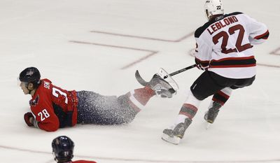 ASSOCIATED PRESS Washington Capitals Alexander Semin (28), of Russia, left, slides across the ice while being defended by New Jersey Devils Pierre-Luc Letourneau-Leblond (22) during the third period of an NHL hockey game in Washington, on Saturday, Oct. 9, 2010. The Capitals won the home game 7-2.