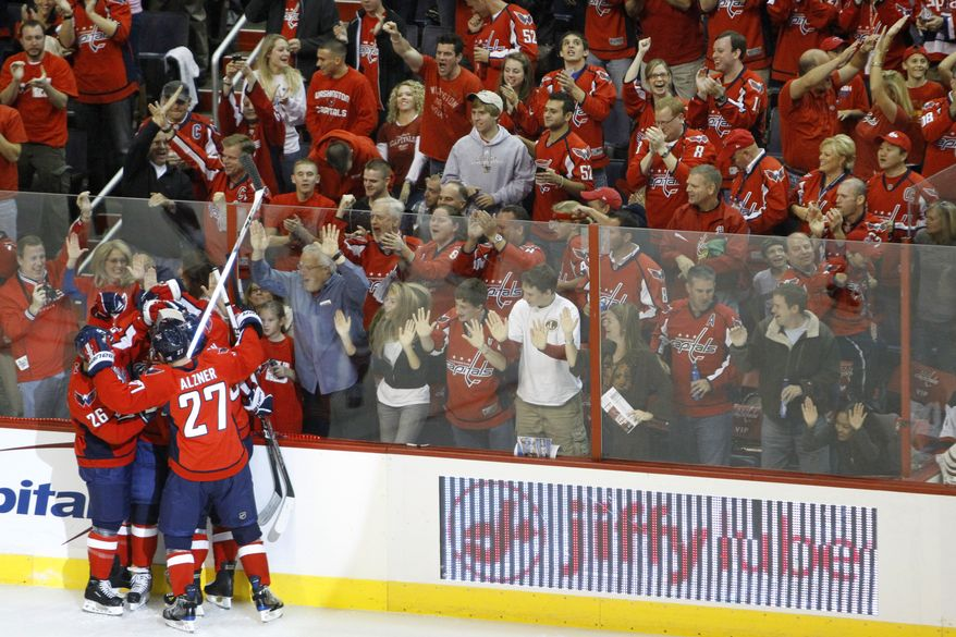 Washington Capitals players and fans celebrate the team's first goal by John Carlson against the New Jersey Devils during the first period of an NHL hockey game in Washington on Saturday, Oct. 9, 2010. (AP Photo)