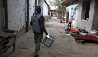 A member of the local electoral committee walks with a ballot box along a street in Osh in southern Kyrgyzstan on Sunday, Oct. 10, 2010. After months of political instability and violence, voters turned out in force for parliamentary elections to choose a new and empowered parliament in the hope that it will usher in a new era of democracy. (AP Photo/Sergey Ponomarev)
