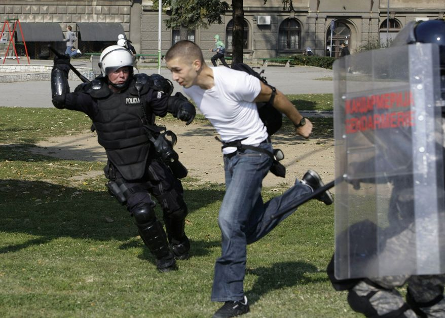 Police attempt to detain a man during anti-gay riots intended to disrupt a gay pride march in Belgrade, Serbia, on Sunday, Oct. 10, 2010. (AP Photo/Darko Vojinovic)