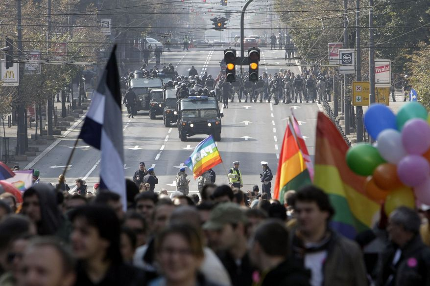 Serbian riot police gather as a gay price parade goes moves along a street in Belgrade, Serbia, on Sunday, Oct. 10, 2010. More than 140 people were hurt and more than 200 arrested, officials said, as police clashed with hundreds of far-right protesters who tried to disrupt the march. (AP Photo/Darko Vojinovic)