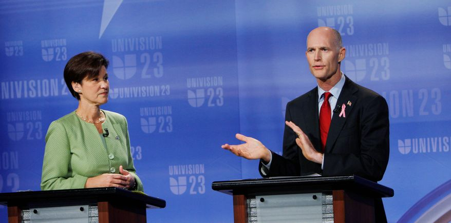 ASSOCIATED PRESS Alex Sink (left) and Rick Scott, Florida gubernatorial candidates, meet for their first face-to-face debate at Univision's studios in Miami on Friday. Their answers to panelists' questions were translated into Spanish.