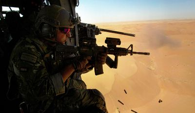 RESCUE READY: Air Force Pararescueman Alejandro Serrano with the 46th Expeditionary Rescue Squadron test-fires his weapon over Kandahar province in case it's needed during casualty-pickup missions in Afghanistan. (Associated Press)