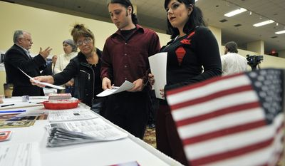 Job seekers browse through information during an Oct. 5 jobs fair sponsored by Scott Lee Cohen, Independent Illinois gubernatorial candidate, in Rockford, Ill. (Associated Press)