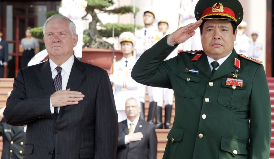 "Defense Secretary Robert M. Gates (left) and Vietnam's minister of defense, Gen. Phung Quang Thanh, stand together during the playing of ""The Star-Spangled Banner"" during a Guards of Honor ceremony at the Ministry of Defense in Hanoi on Monday, Oct. 11, 2010. (AP Photo/Carolyn Kaster, Pool)"