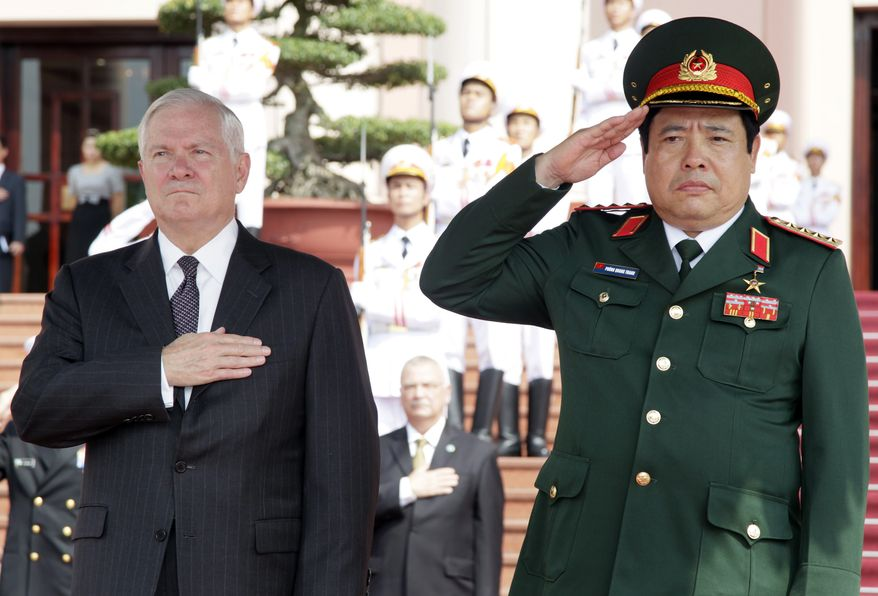 """Defense Secretary Robert M. Gates (left) and Vietnam's minister of defense, Gen. Phung Quang Thanh, stand together during the playing of """"The Star-Spangled Banner"""" during a Guards of Honor ceremony at the Ministry of Defense in Hanoi on Monday, Oct. 11, 2010. (AP Photo/Carolyn Kaster, Pool)"""