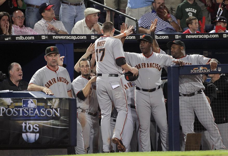 ASSOCIATED PRESS San Francisco Giants' Aubrey Huff (17) is congratulated by teammates after scoring during the seventh inning on a fielders choice in Game 4 of baseball's National League Division Series against the Atlanta Braves on Monday, Oct. 11, 2010, in Atlanta.
