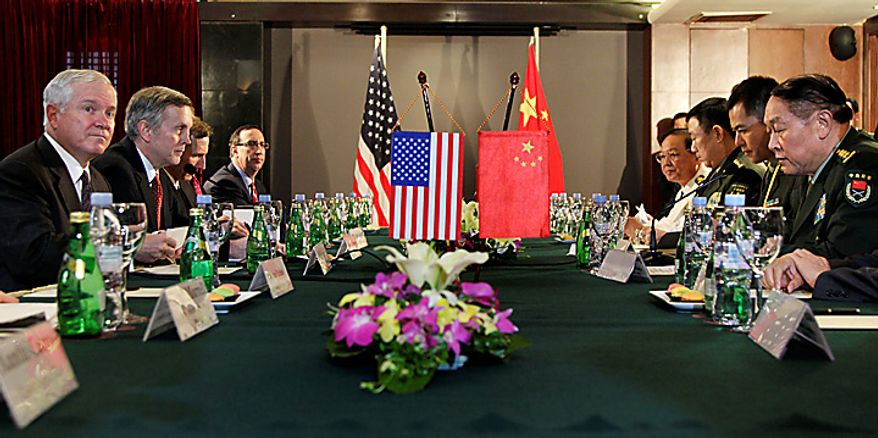 Defense Secretary Robert Gates, left, and China's Minister of Defense Liang Guanglie, right sit down for a meeting in Hanoi, Vietnam, Monday, Oct. 11, 2010.  (AP Photo/Carolyn Kaster, Pool)
