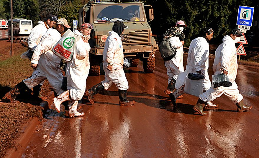 Volunteers, wearing protective gears, walk across a street covered by toxic red sludge in Devecser, Hungary, Monday, Oct. 11, 2010. (AP Photo/Bela Szandelszky)
