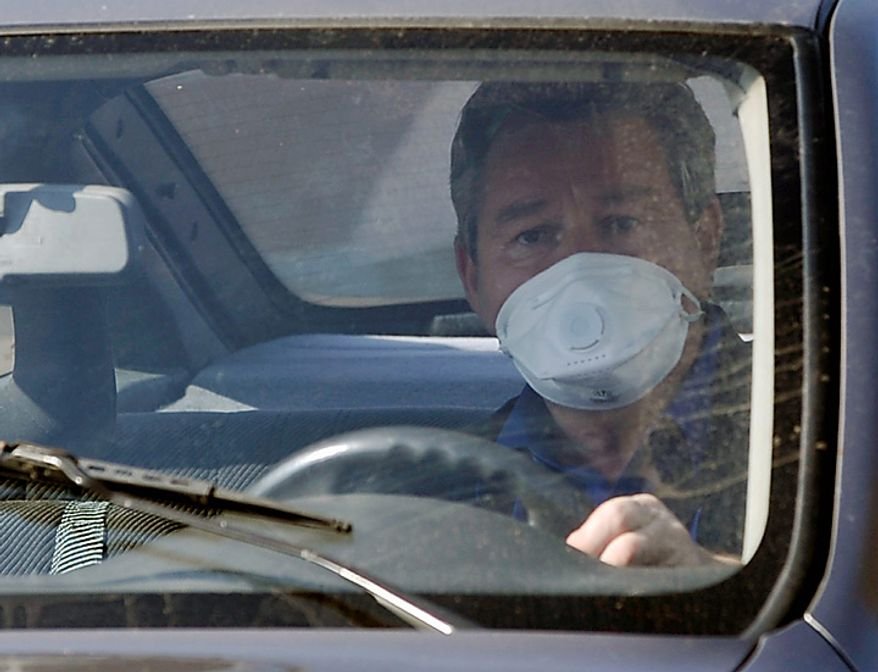A resident, wearing a protective mask, drives his car in Devecser, Hungary, Monday, Oct. 11, 2010. (AP Photo/Bela Szandelszky)
